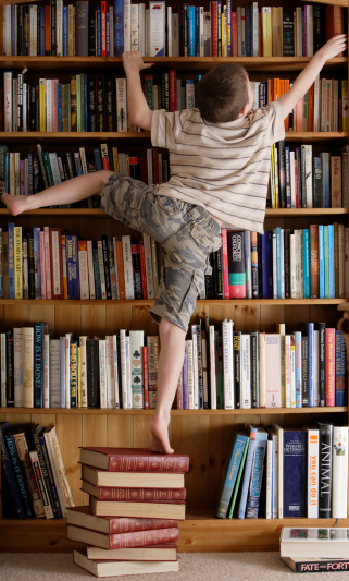 Boy (8-9) standing on book reaching for top book shelf, rear view